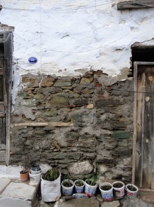 Bare stone wall between wooden doors, plaster above, plant pots below, Şirince, January, 2018