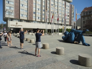 Human tourists photographing sculptured supine blue ape with chrome testicles outside the Intercontinental Hotel, Prague