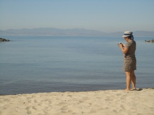 Woman on the shore, looking at her mobile