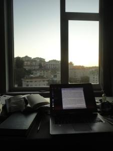 Computer on table by window at dawn
